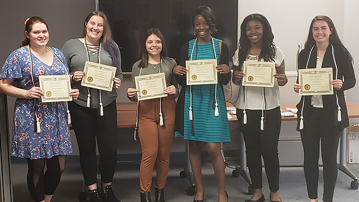 Caldwell University students showing their achievements certification.